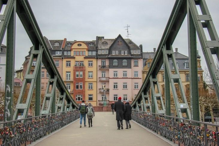 Walking across Eiserner Steg Iron Bridge in Frankfurt, Germany
