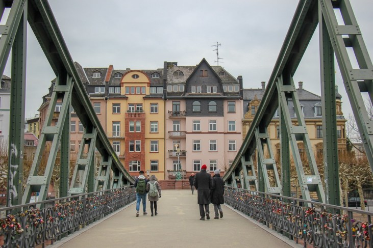 Walking across Eiserner Steg Iron Bridge in Frankfurt, Germany
