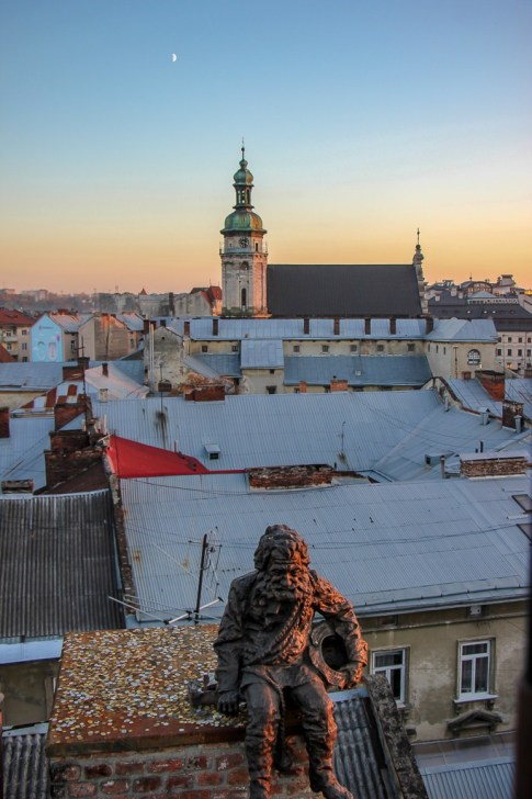 Chimney sweeper statue and Good Luck Well on rooftop of House of Legends in Lviv, Ukraine
