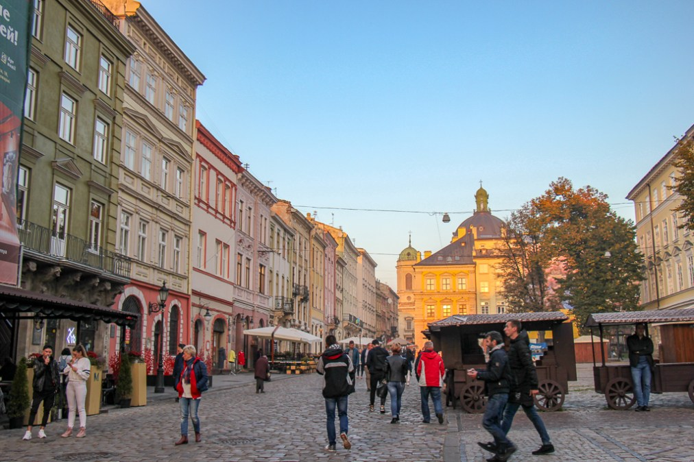 People on Rynok Square at sunset in Lviv, Ukraine