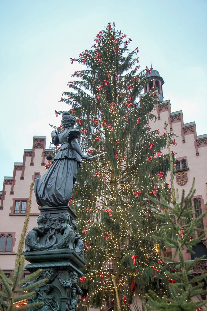 Fountain of Justice faces giant Christmas Tree in Romerberg in Frankfurt, Germany