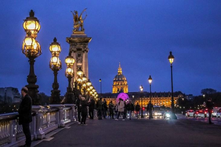 Street lamps glow on Pont Alexandre III Bridge in Paris, France