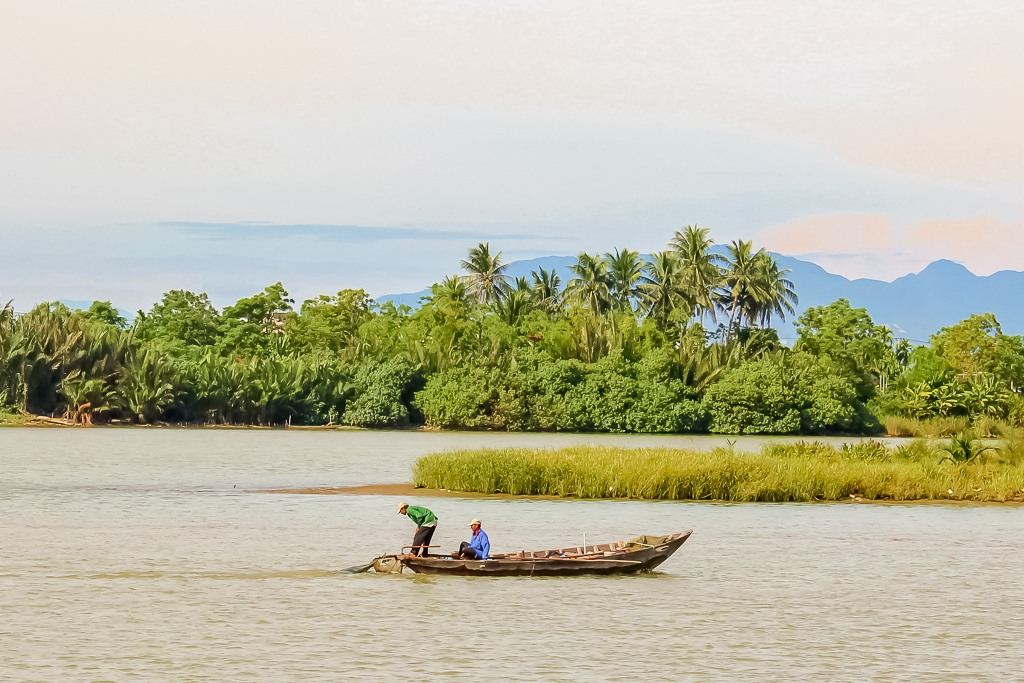 Fisherman tending to nets on Thu Bon River in Hoi An, Vietnam