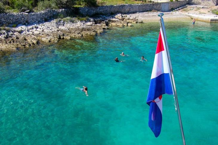 Boat passengers swim in cove on Brac Island, Croatia