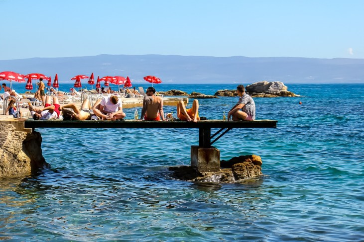 Boys sit on pier at Bacvice Beach in Split, Croatia