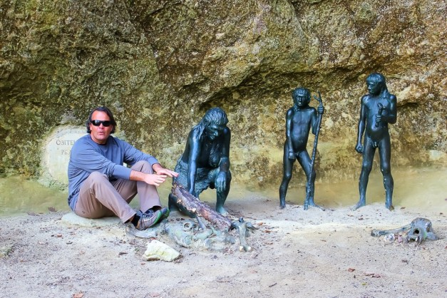 Kris sits with Neanderthal statues at excavation site in Krapina, Croatia