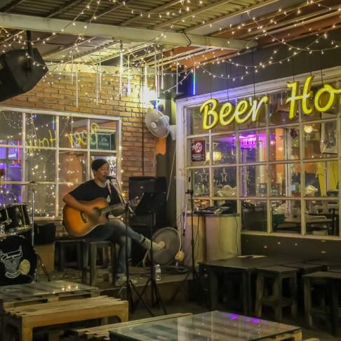 Man plays guitar at Beer House bar at Train Night Market in Bangkok, Thailand
