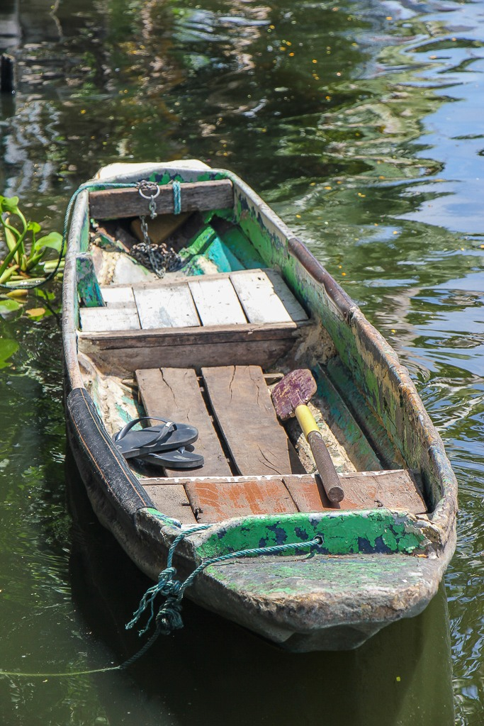 Old wooden row boat on canal in Bangkok, Thailand