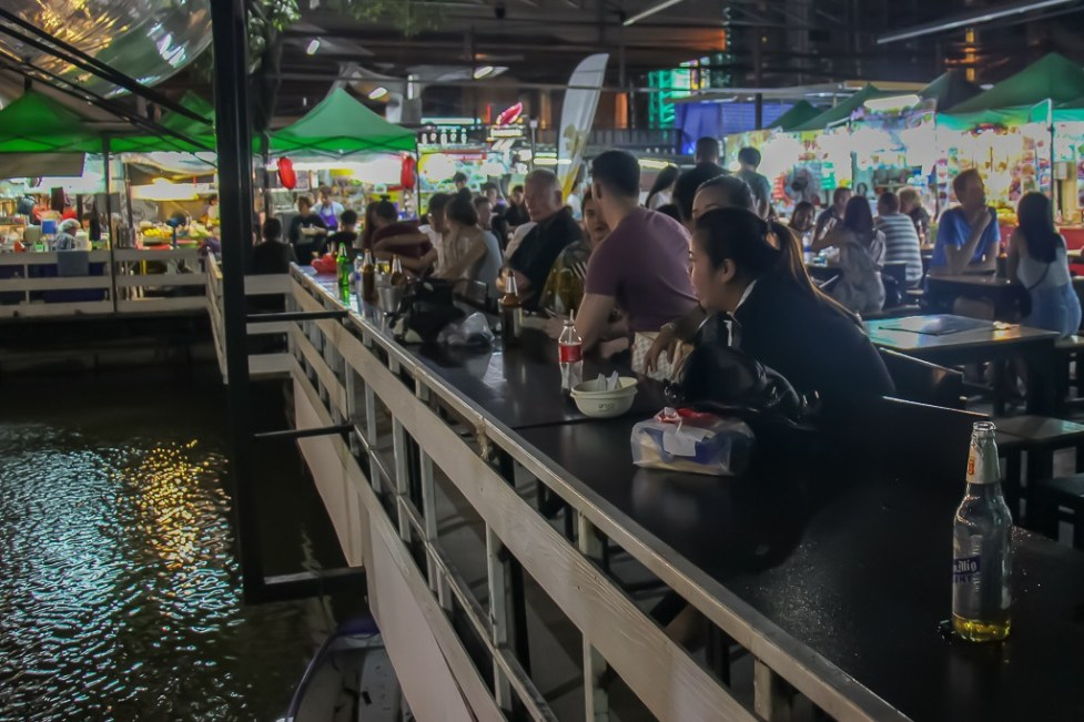 Diners sit next to pond at The Corner 79 Food Market in Bangkok On Nut, Thailand