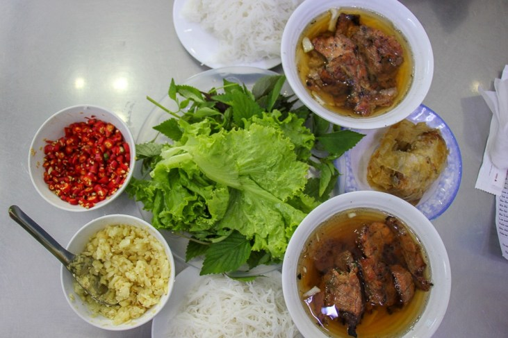 Bowls of Bun Cha and accompaniments at Bun Cha Huong Lien in Hanoi, Vietnam