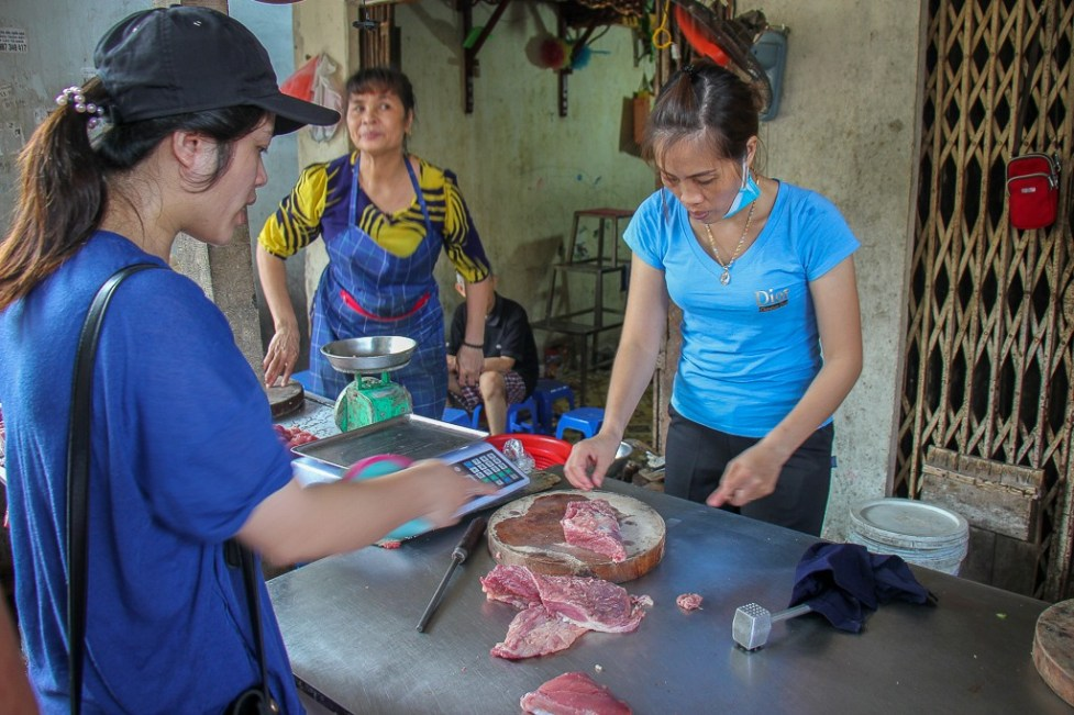 Chef from Rose Kitchen Hanoi Cooking Class buys meat from local vendor