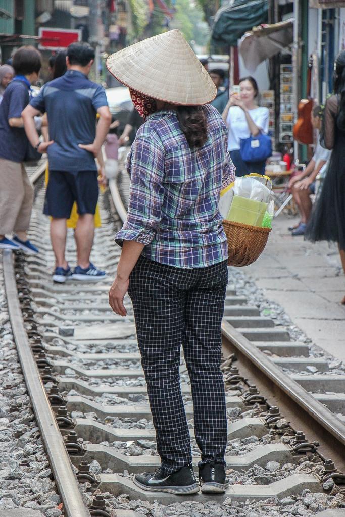 Girl sells food on train tracks in Hanoi, Vietnam
