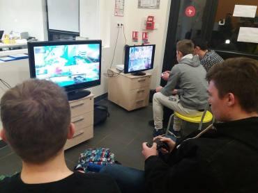 Quatre jeunes jouent sur deux écrans et deux consoles distincts