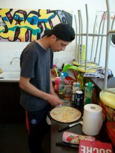 Matéo est en train de sortir sa pizza pour la mettre ensuite au four
