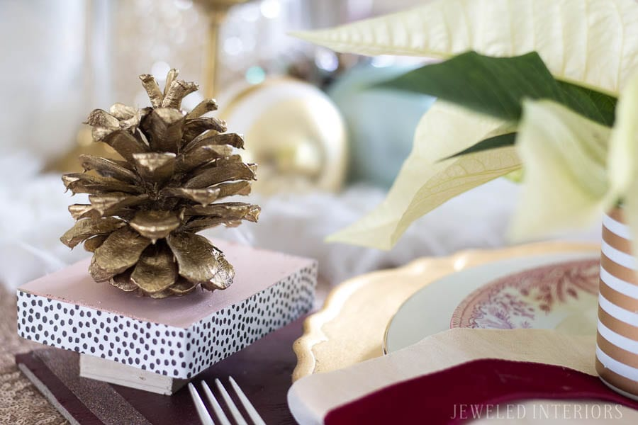 Pinecone dinner party|| THIS DINING ROOM! Looking for inspiration for a eclectic, chic, and glam Christmas? Jeweled Interiors, Holiday, Home Tour, Burgundy, cranberry, blush, Decor, Ideas, Tips, wreaths, Christmas, tree, decor, decorations, DIY, inspiration, red, maroon, wine, home tour, poinsettia, glam, chic, peach, gold, black, white, Panton, chairs, brass, chandelier, tablescape, pinecones