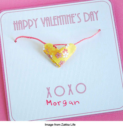 Necklace with paper origami heart pendant presented on a Valentine's day card.