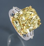 The rare-colored 13.22-carat diamond is flanked by two bullet-cut diamonds and set in 18k yellow gold and platinum.