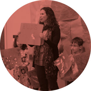 A woman who looks to be passionate and enthusiastic standing next two young children as they all hold up pictures and posters that they each created. They are showing them to an audience and speaking about them.