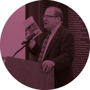 A man wearing a suit and glasses, standing in front of a microphone and holding up a pamphlet. He is passionately giving a speech.
