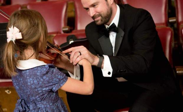 Melrose Schools Orchestra Director Luke Miller, seen here assisting a young student with the violin, has been named the state's Orchestra Director of the Year. (Courtesy Photo/Melrose Symphony Orchestra)