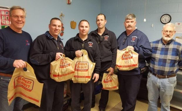 Members of the Rochester Fire Department pose with bags of food that will go to city children to help ensure that they have healthy meals to eat during the weekend days when they are away from school. Pictured left-to-right: Dave Bogan, Jason Laferte, Matthew Parker, Mike George, Chief Mark Klose, Former Mayor John Larochelle (Courtesy photo)