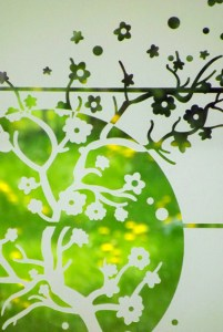 cerisier japonais en dépoli posé sur une vitre avec en fond un jardin