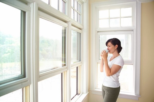 Jeune femme qui boit son café devant ses fenêtres