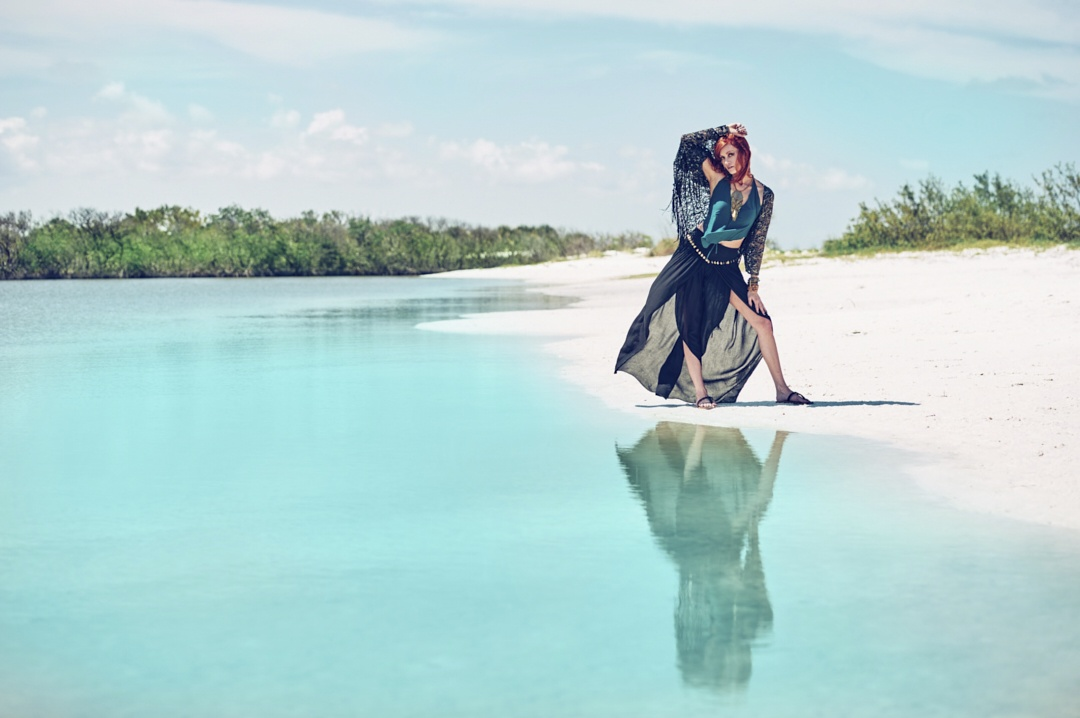 Red head model posing in bohemian skirt and top at the beach photographed by JHR Photography