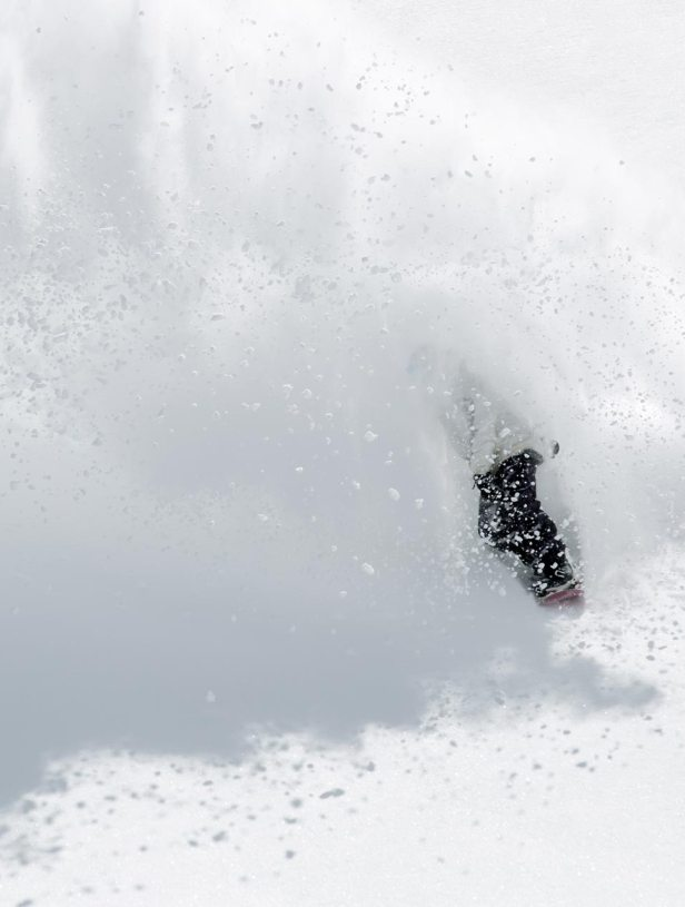 Snowboarder completely covered in powder.
