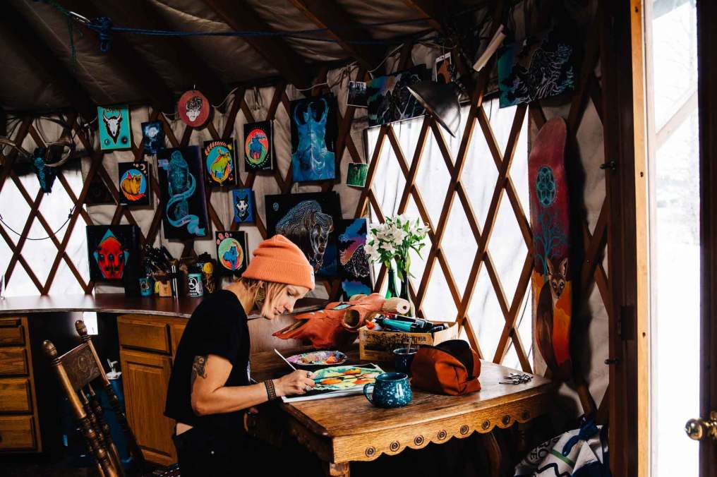 Artist Marinna Elinski working on a new illustration in her yurt.