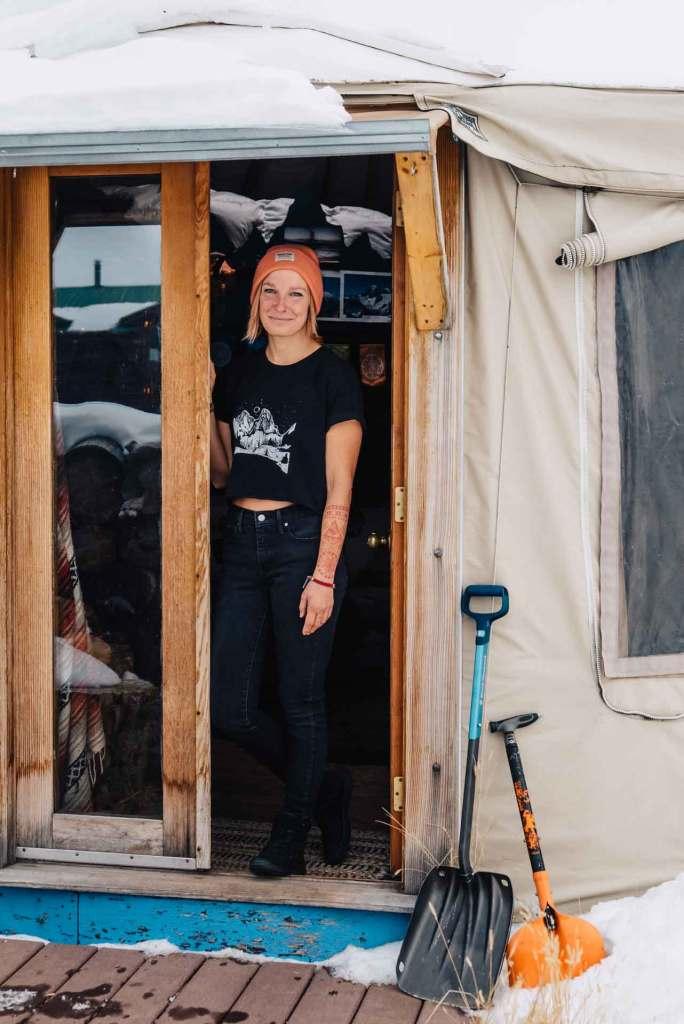 Marinna Elinski standing in the doorway of her yurt.