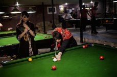 Two women play pool at a billiards hall, where only men are supposed to be allowed.