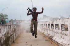 Joseph Duo, a Liberian militia commander loyal to the government, exults after firing a rocket-propelled grenade at rebel forces at a key strategic bridge, July 20, 2003. Chris Hondros/Getty Images