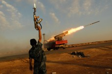 A rebel fighter celebrates as his comrades fire a rocket barrage toward the positions of troops loyal to Libyan ruler Muammar Gaddafi, April 14, 2011. Chris Hondros/Getty Images
