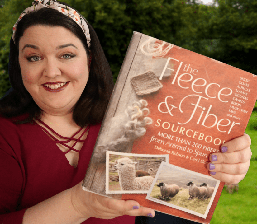 Evie holds up a copy of the Fleece and Fiber Source Book.
