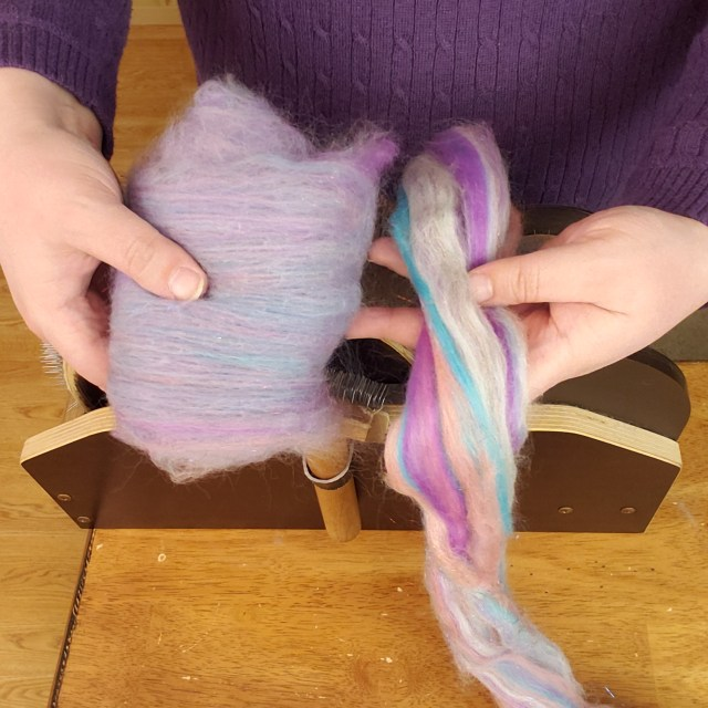 A wool batt and a strip of combed top are held above a drum carder. The batt is a blended lavender color and the combed top has stripes of pink, peach, blue, and grey wool.