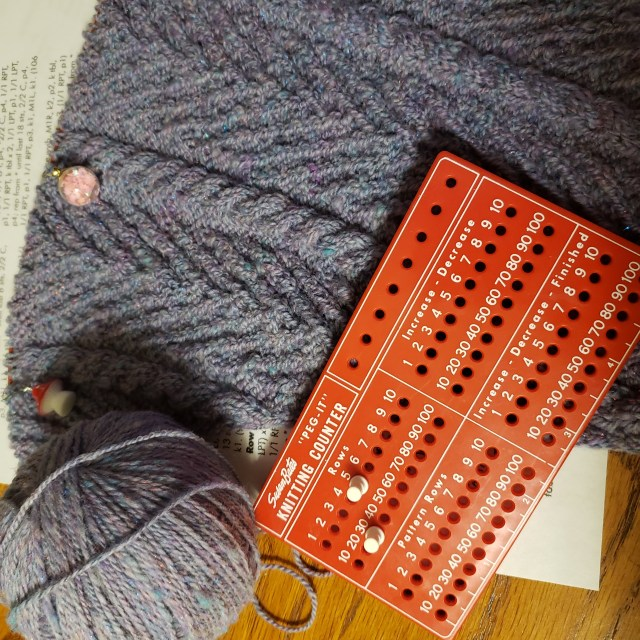 The hand knit Whiria Cowl is laid out next to a ball of handspun yarn. A red knitting counter with pegs marking the numbers 5 and 30 sits on top of the knitting.