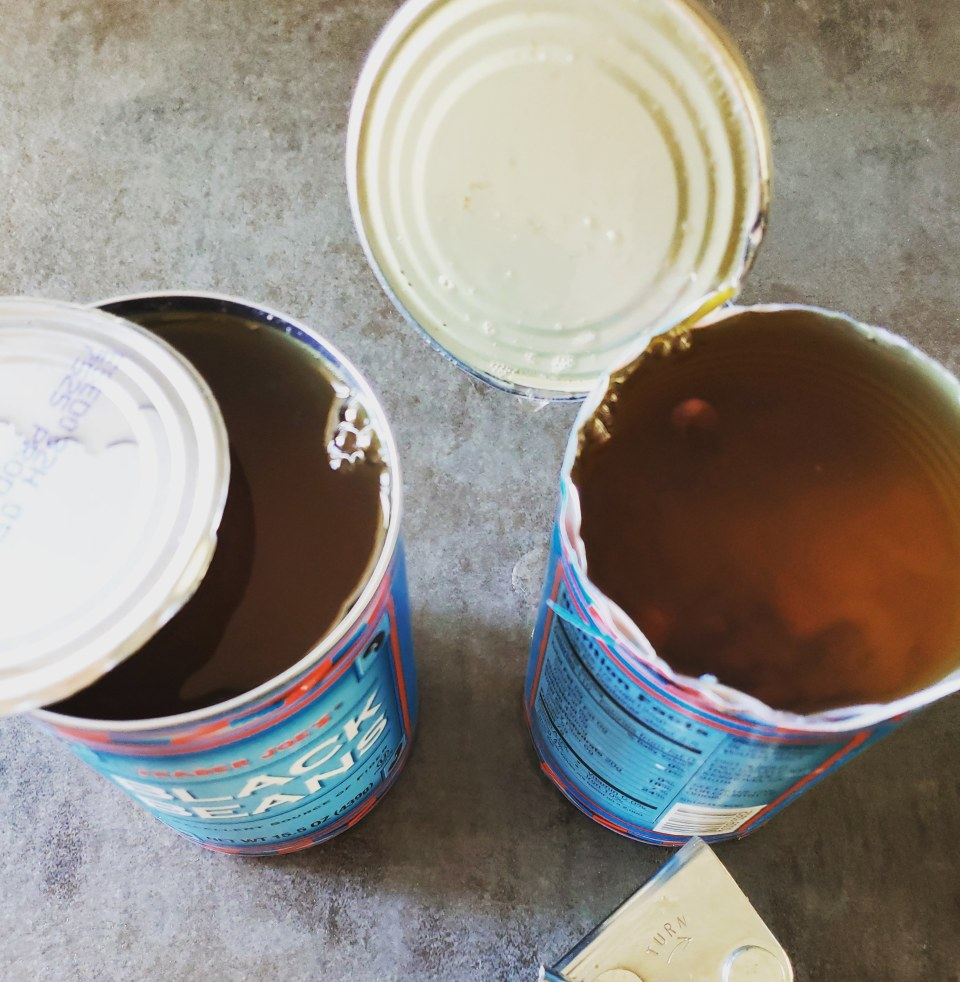 Two opened cans of beans using two methods of opening the can