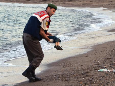 Police officer carrying Aylan Kurdi