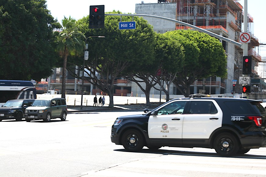 A police SUV cruises by on Hill street in downtown Los Angeles