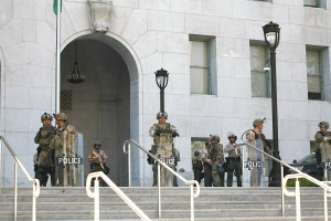 A combination of police officers, sheriffs, and national guard service-members stand at the Hall of Justice in downtown Los Angeles