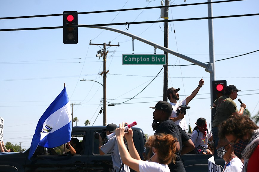 Marchers atop a pick-up truck make their way past a Compton boulevard sign en route to the Compton sheriff department station