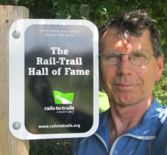 Jim-Schmid-next-to-Rail-Trail-Hall-of-Fame-sign-on-Virginia-Creeper-Trail-Damascus-VA-07-10-2016