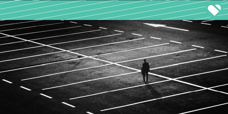 man standing alone in empty parking lot. black and white.