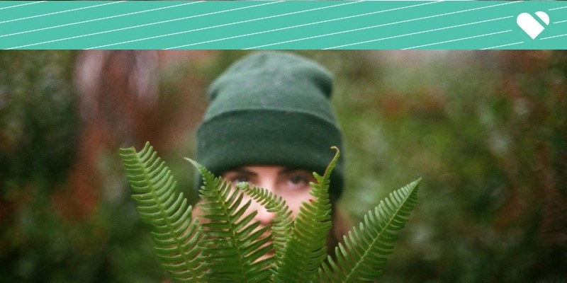 Woman hiding behind leaves in forested background.