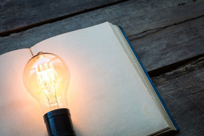 vintage book and light bulb on wood table