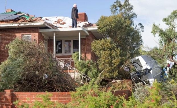 เจ้าของบ้านขึ้นไปสำรวจความเสียหายบนหลังคาในขณะมีเรือลอยมาตกข้าง ๆ