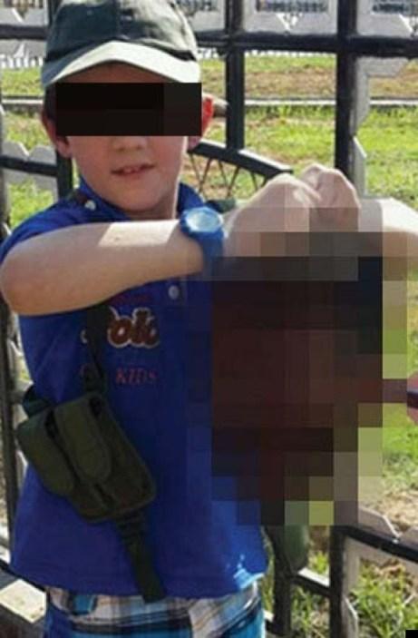 เด็กชายวัย 7 ขวบเชื่อว่าเป็นบุตรชายของนาย Khaled Sharrouf  กำลังชูหัวชาวมุสลิมต่างนิกายแกว่งเล่นในซีเรีย