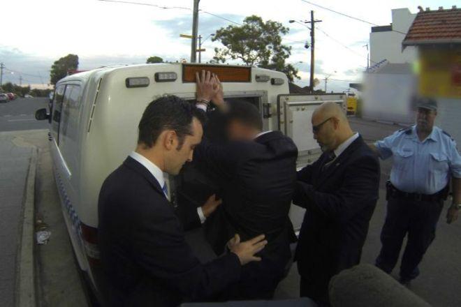 นาย Mark Caleo ขณะถูกจับกุมจากบ้านที่ย่าน Ramsgate (ภาพจากสำนักข่าว ABC)