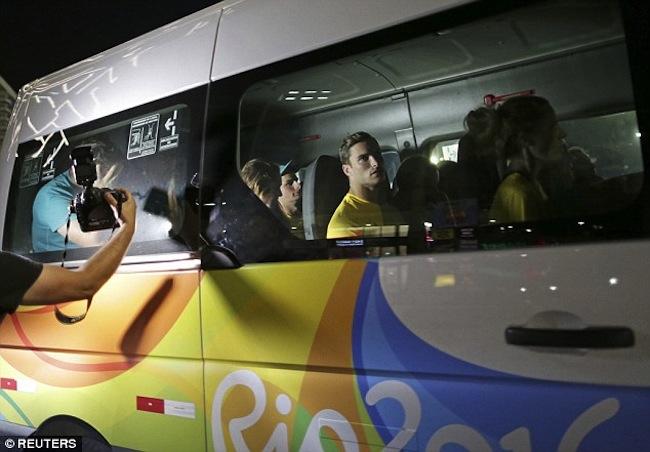นักกีฬาออสซี่ 10 คนภายในรถมินิแวนเพื่อกลับบ้านพักนักกีฬา : ภาพจาก dailymail.co.uk ต้นฉบับสำนักข่าว Reuters